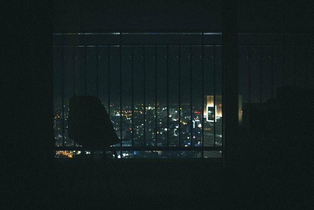 Pohľad na nočné mesto cez balkón s nerezovým zábradlím.jpg