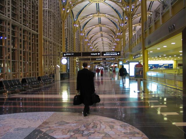 Muž v čiernom kabáte kráča po letisku, batožina, businessman