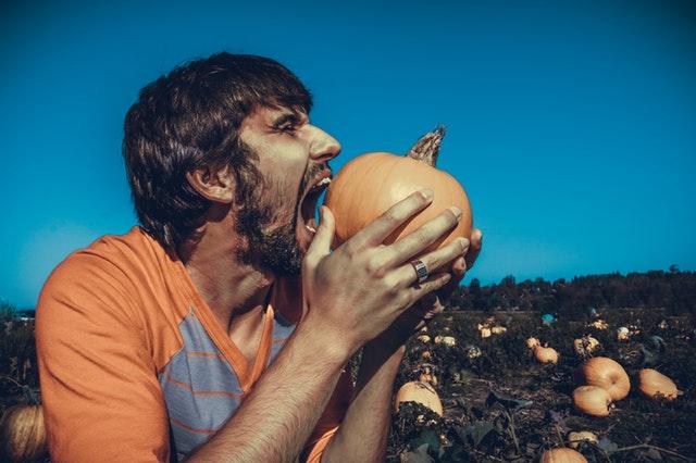 Muž v oranžovom tričku na tekvicovom poli hryzie do tekvice