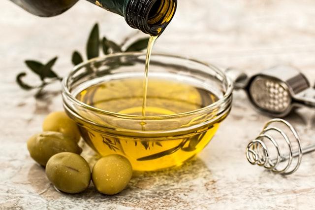 Olivový olej sa leje do misky, vedľa ktorej ležia zelené olivy