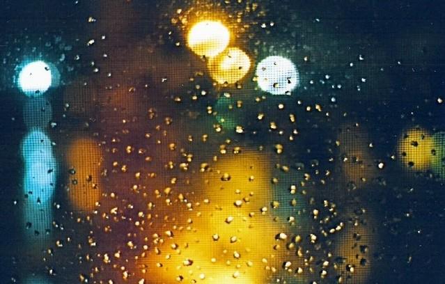 Pohľad cez sklo na nočnú ulicu so svetlami.jpg
