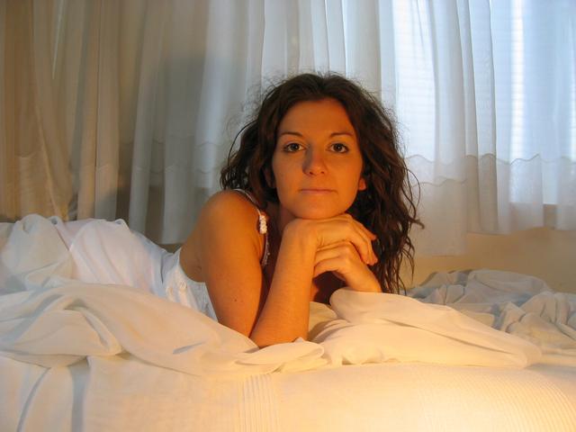 Žena v posteli, záclony, priamy pohľad