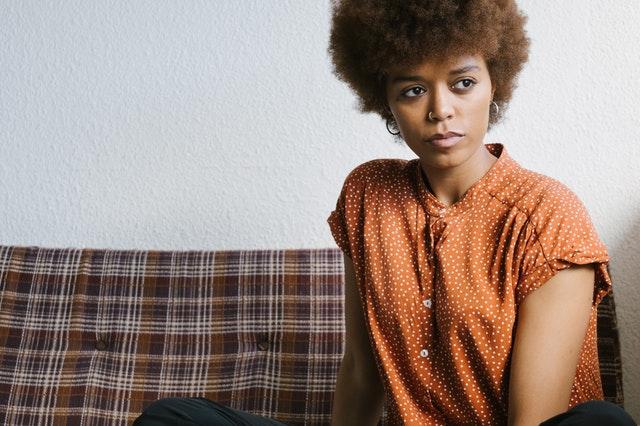 Žena v oranžovej blúzke s okrúhlymi náušnicami sedí na gauči.jpg