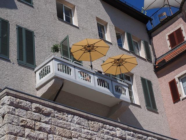 Balkón na veľkom dome s dvoma oranžovými slnečníkmi.jpg