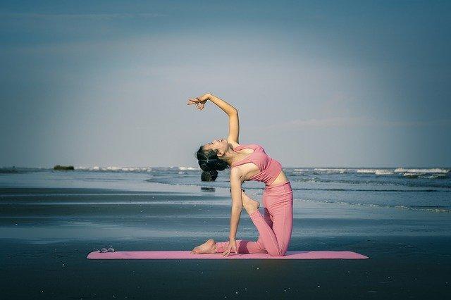 Žena v ružovom oblečení cvičí jogu